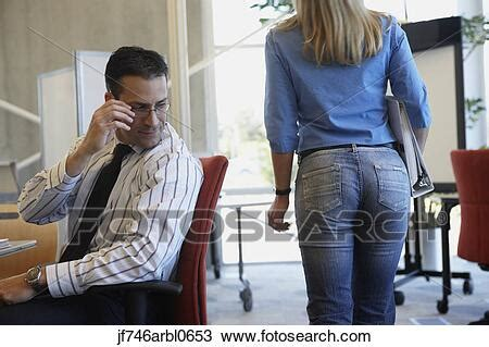 Stock Photo of Businessman checking out female coworker