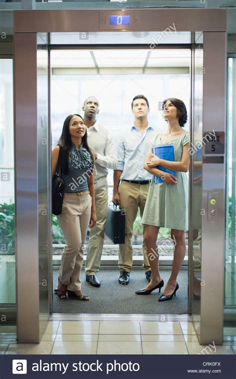 Business people riding glass elevator Stock Photo